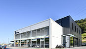 Halle logistique et bâtiment commercial, nouvelle station-service et station de lavage pour véhicules pour Faucherre Transport SA à Moudon